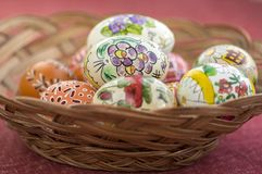 Colorful painted Easter eggs in brown wicker basket, traditional Easter still life, painted flowers Royalty Free Stock Photo