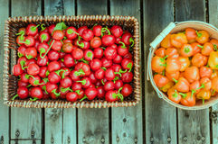 Red and orange peppers in baskets Stock Photos