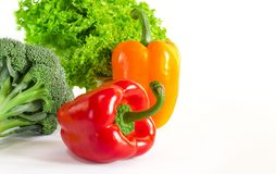 Juicy red and orange peppers with a green tail lies next to Bundle of lettuce and broccoli are on a white background royalty free stock images