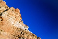 Red and Orange Rock Cliff Face. Red and orange rocks form a cliff face above the hot sands of the desert floor stock images