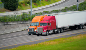 Red orange semi trucks trailers driving highway road together Royalty Free Stock Photo