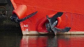 Red-orange ship with ship anchor. Anchor on the side and at the bow Stock Photography