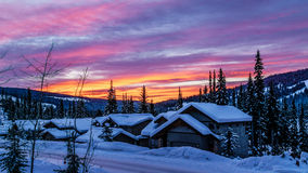Red and Orange sky at a sunrise over the snow covered houses in the alpine village of Sun Peak Royalty Free Stock Images