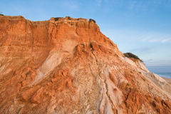 Red orange soil cliffs rising up in blue sky on beach falesia Stock Photography