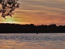Red / orange sunset, evening landscape looking over a lake, photo taken in the UK. Red / orange sun setting sunset, evening landscape looking over a lake, photo royalty free stock photography
