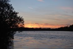Red / orange sunset, evening landscape looking over a lake, photo taken in the UK. Red / orange sun setting sunset, evening landscape looking over a lake, photo stock photography