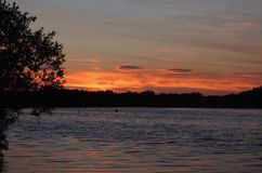 Red / orange sunset, evening landscape looking over a lake, photo taken in the UK. Red / orange sun setting sunset, evening landscape looking over a lake, photo stock image