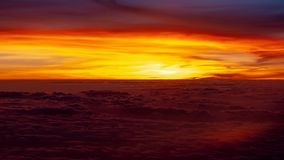 Red and orange sunset over clouds as seen from an airplane royalty free stock photography