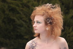 Red Orange Teased Hair with Dead Flowers. A woman with green eye make up and a puzzle piece tattoo looking to the side Stock Photo
