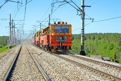Red-orange trolley does run on railway tracks Stock Photography