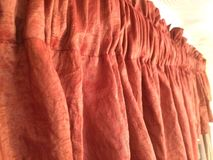 Red-orange valance window treatment. Rust orange colored shorted 2 rod pocket valance bindis covering topper. Nice crinkle fabric interior decor for the designer Stock Photography