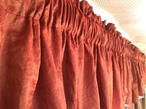 Red-orange valance window treatment. Rust orange colored shorted 2 rod pocket valance bindis covering topper. Nice crinkle fabric interior decor for the designer Royalty Free Stock Photo