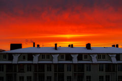 Red, orange, vivid sky at sunrise over the building in the city. Royalty Free Stock Image