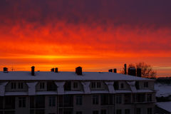 Red, orange, vivid sky at sunrise over the building in the city. Stock Photos