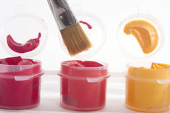 Red Orange Yellow Acrylic Paints and Paintbrush Stock Photo