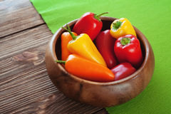 Red, orange, yellow bell pepper in wooden bowl on green napkin. Red, orange, yellow bell pepper Royalty Free Stock Photography