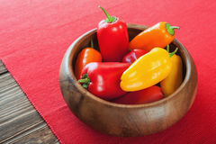 Red, orange, yellow bell pepper in wooden bowl on a red napkin. Red, orange, yellow bell pepper Royalty Free Stock Photos