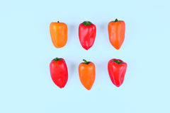 Red, orange, yellow paprika on blue background. Royalty Free Stock Photography