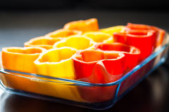 Red, orange and yellow peppers getting prepared for cooking Stock Photo