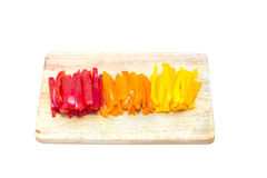 Red orange yellow peppers sliced on a cutting board Royalty Free Stock Image