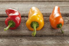 Red, orange and yellow sweet peppers on a rough wood surface Stock Photo