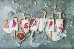 Red orange, yogurt, granola popsicles on ice cubes, grey background stock photos
