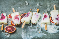 Red orange, yogurt, granola popsicles on ice cubes, healthy dessert Royalty Free Stock Photo