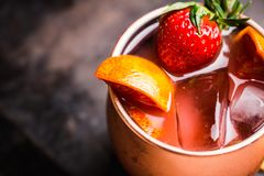 Red oranges and strawberry cocktail in copper mug variation of Moscow mule on the wooden background. Selective focus. Shallow depth of field royalty free stock photos