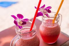 Red Orchid flower on glass mug Smoothies beverage in the summer. Shallow depth of field. Cool drinks. Red Orchid flower on glass mug Smoothies beverage in the stock photo
