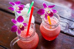 Red Orchid flower on glass mug Smoothies beverage in the summer. Shallow depth of field. Cool drinks. Red Orchid flower on glass mug Smoothies beverage in the royalty free stock photo
