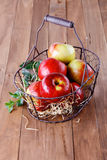 Red organic apples in a metal basket on wooden background. Healthy organic red apples in a metal basket on a wooden background stock photography