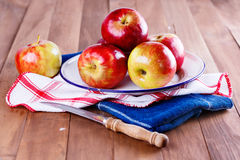 Red organic apples in a metal plate on wooden background. Healthy organic red apples in a metal rustic plate and knife on a wooden background royalty free stock images