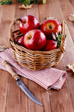 Red organic apples in a straw basket on wooden background. Healthy organic red apples in a straw basket and knife on a wooden background stock image