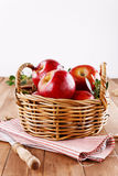 Red organic apples in a straw basket on wooden background. Healthy organic red apples in a straw basket and knife on a wooden background stock photos