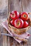 Red organic apples in a straw basket on wooden background. Healthy organic red apples in a straw basket and knife on a wooden background royalty free stock image