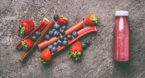 Red organic fruits and berries smoothie with rhubarb, blueberries and strawberries in bottle on gray granite table , top view. Hea. Lthy dieting and antioxidant stock image