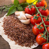 Red organic  rice, tomatoes, olive oil, garlic and herbs on wood Stock Photo