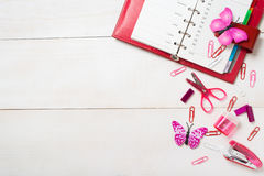 Red organizer and pink stationary on the wooden table Stock Photos