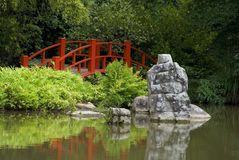 Red Oriental Bridge. Red-orange Oriental bridge by pond Royalty Free Stock Image