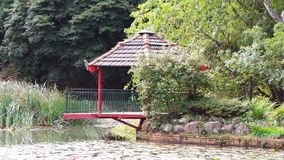 Red oriental building over a pond Stock Images