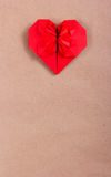 Red origami heart on a paper background. Valentine on a background of recycled paper. Stock Photos