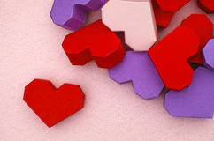 Red origami heart with some other hearts. On pink background Royalty Free Stock Image