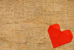 Red origami paper heart on wooden texture close-up background Royalty Free Stock Photos