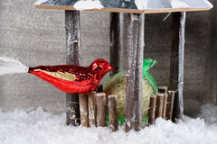 Red ornament bird finding seed in winter Stock Photography