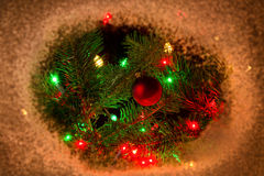 Red ornament hanging on fir tree branch with lights and surround Stock Images