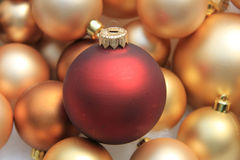 Red ornament on a pile of golden ornaments Royalty Free Stock Photos