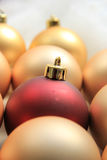 Red ornament on a pile of golden ornaments Royalty Free Stock Images