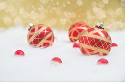 Red ornaments on gold background. Red ornaments arranged on white fur with gold twinkling lights in background Stock Photo