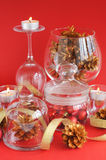 Red ornaments in jar, candles and pine cones Royalty Free Stock Image