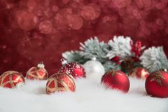 Red ornaments on twinkling background. Red ornaments arranged on fur with red twinkling lights in background Royalty Free Stock Photo